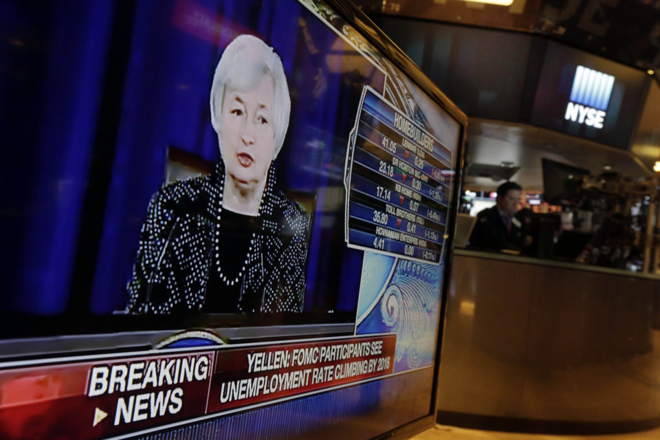 Photo - Federal Reserve Chair Janet Yellen's news conference appears on a television monitor on the floor of the New York Stock Exchange, Wednesday, June 18, 2014. The Federal Reserve says it will further slow the pace of its bond purchases because a strengthening U.S. job market needs less support. But it's offering no clear signal about when it will start raising its benchmark short-term rate.  (AP Photo/Richard Drew)