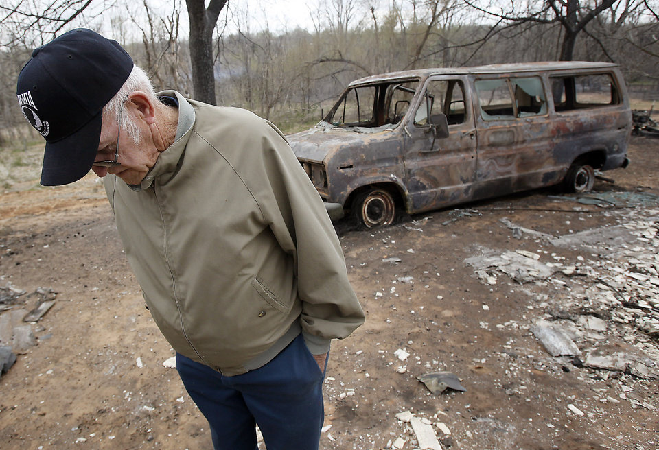 Photo - Tex Cyr lowers his head as he walks through the remains of his home that was destroyed by wildfires on Friday, April 10, 2009, in Choctaw, Okla.  Photo by Chris Landsberger, The Oklahoman