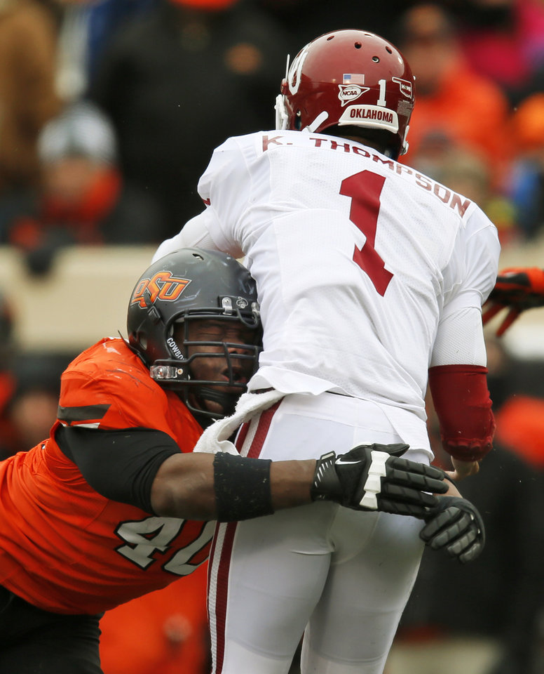 Photo - Oklahoma State's Tyler Johnson (40) pressures Oklahoma's Kendal Thompson (1) during the Bedlam college football game between the Oklahoma State University Cowboys (OSU) and the University of Oklahoma Sooners (OU) at Boone Pickens Stadium in Stillwater, Okla., Saturday, Dec. 7, 2013. OU won, 33-24. Photo by Nate Billings, The Oklahoman