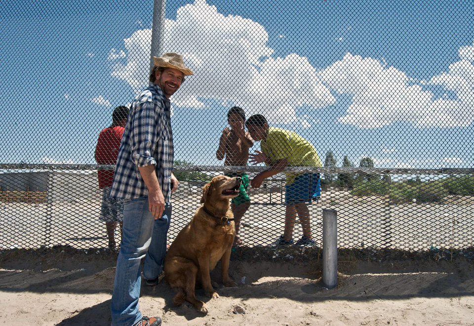Photo - In this 2010 photo provided by Explore.org,, philanthropist Charlie Annenberg, left, stands with his golden retriever, Lucky, while filming a documentary at the Mexican border of Ciudad Juarez, the border town with El Paso, Texas. For 16 years, Lucky has been his sidekick, soul mate and inspiration, said Annenberg.  In 2010, Annenberg started Dog Bless You, a journal of their travels as told by Lucky but written by Annenberg. (AP Photo/Explore.org)