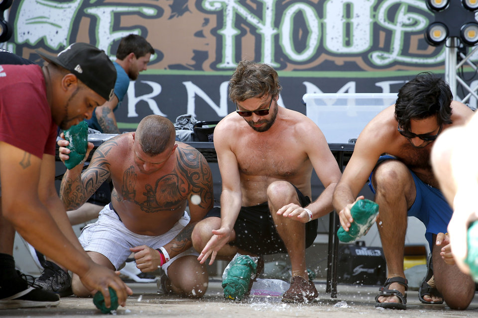 Photo - Contestants in the Mens Only Wet T-shirt Contest try to break open frozen shirts  an put them on during the Okie Noodling Tournament and Festival at Wacker Park in Pauls Valley, Okla., Saturday, June 15, 2019. [Bryan Terry/The Oklahoman]