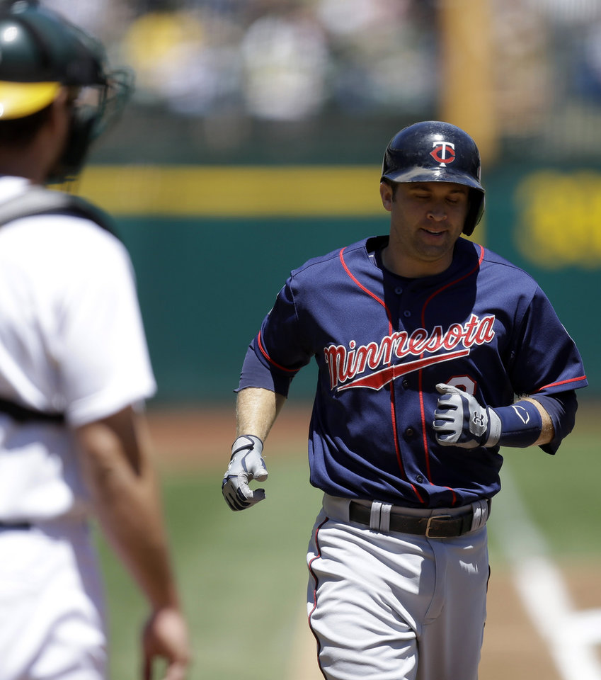 Photo - Minnesota Twins' Brian Dozier, right, runs the bases after hitting a home run off Oakland Athletics' Jason Hammel in the first inning of a baseball game Sunday, Aug. 10, 2014, in Oakland, Calif. (AP Photo/Ben Margot)