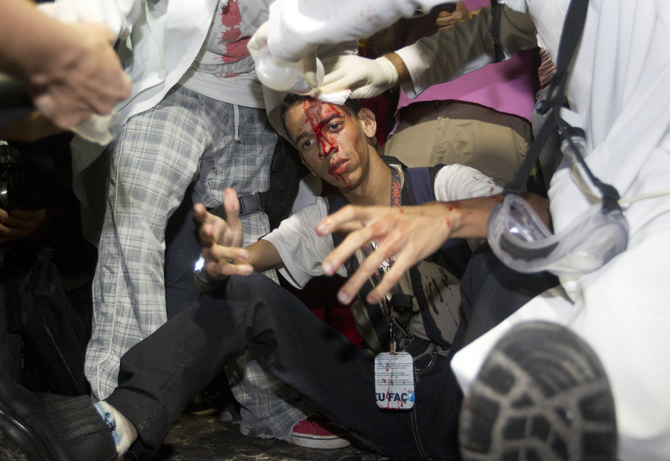 Photo - A demonstrator is assisted by paramedics after he was injured by a rock thrown during a march against the FIFA 2014 soccer World Cup, in Copacabana beach, Rio de Janeiro, Brazil, Thursday, June 12, 2014. The demonstrators are demanding better public services and protesting the money spent on the soccer tournament. (AP Photo/Leonardo Wen)