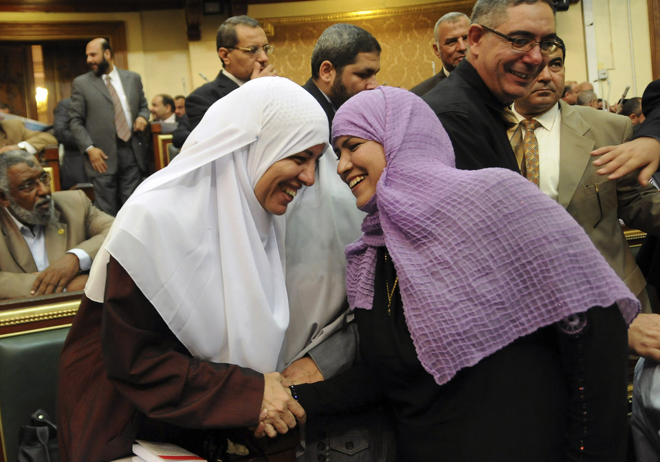 Two female Egyptian lawmakers greet each other at a brief session of Parliament, the first since the country's high court ruled the chamber unconstitutional, in Cairo, Egypt, Tuesday, July 10, 2012. Egypt's Islamist-dominated parliament convened Tuesday in defiance of a ruling by the country's highest court and swiftly voted to seek a legal opinion on the decision that invalidated the chamber over apparent election irregularities. (AP Photo/Mohammed Asad) ORG XMIT: CAI103