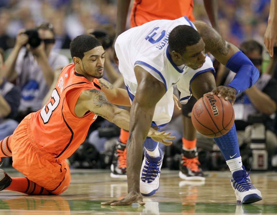 Kentucky's Terrence Jones, right, fights for a loose ball with Louisville's Peyton Siva during the first half of an NCAA Final Four semifinal college basketball tournament game Saturday, March 31, 2012, in New Orleans. (AP Photo/Mark Humphrey)