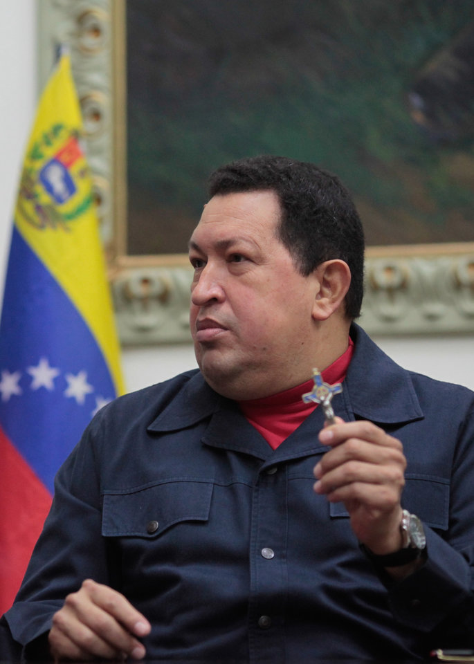 Photo - In this photo released by Miraflores Press Office, Venezuela's President Hugo Chavez holds up a crucifix  during a televised speech form his office at Miraflores Presidential palace in Caracas, Venezuela, Saturday, Dec. 8, 2012. Chavez announced Saturday night that his cancer has returned and that he will undergo another surgery in Cuba. Chavez, who won re-election on Oct. 7, also said for the first time that if his health were to worsen, his successor would be Vice President Nicolas Maduro.(AP Photo/Miraflores Press Office, Marcelo Garcia)