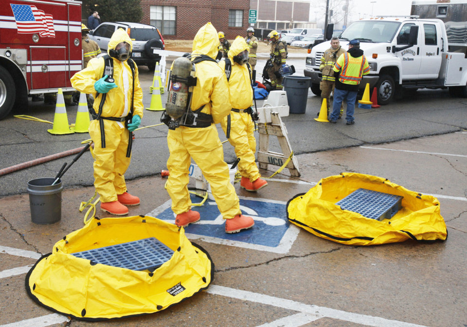 Photo - Emergency workers wear protective suits during a simulated emergency exercise Thursday at the University of Central Oklahoma. Photos by Paul Hellstern, The Oklahoman