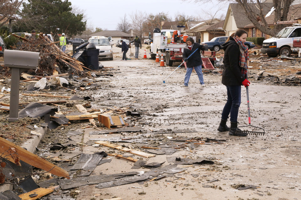 Photo - Residents clean debris from the street in front of a house which exploded at 12409 Whispering Hollow Drive in Oklahoma City, OK, Saturday, January 2, 2016. The cause of the explosion is being investigated. Photo by Paul Hellstern, The Oklahoman