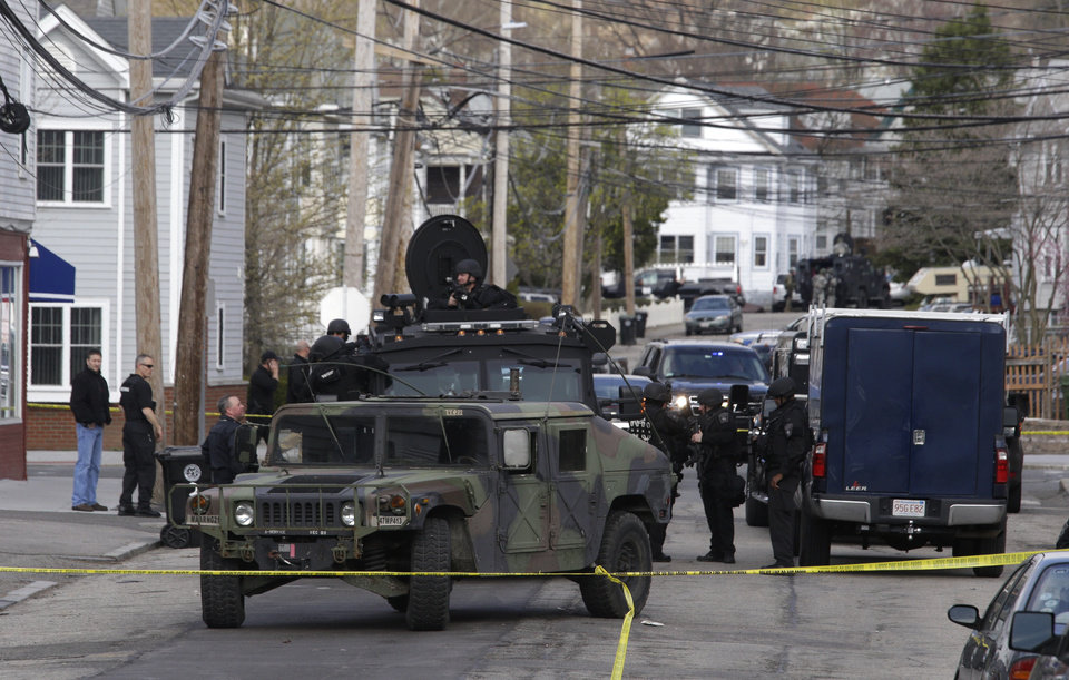 Photo - Officials wearing tactical gear stand near an armored vehicle as they search an apartment building for one of two suspects in the Boston Marathon bombing, in Watertown, Mass., Friday, April 19, 2013.  Two suspects in the Boston Marathon bombing killed an MIT police officer, injured a transit officer in a firefight and threw explosive devices at police during a getaway attempt in a long night of violence that left one of them dead and another still at large Friday, authorities said as the manhunt intensified for a young man described as a dangerous terrorist. (AP Photo/Julio Cortez)