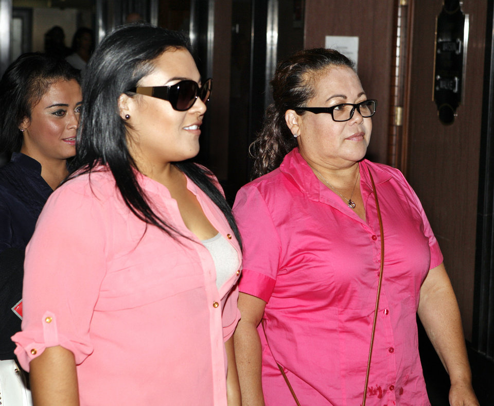 Photo - Monica Salazar Orozco and her mother, Elizabeth Hinojosa, of Jourdanton, Texas, walk to the courtroom Wednesday to plead guilty at the Oklahoma County Courthouse. Hinojosa, a dental assistant and her daughter, a dental receptionist, both pleaded guilty to practicing dentistry without a license. Photo by Paul B. Southerland, The Oklahoman  PAUL B. SOUTHERLAND - PAUL B. SOUTHERLAND