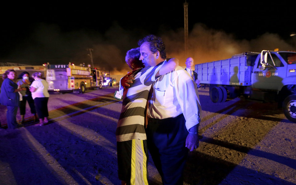 Photo - New Jersey Gov. Chris Christie, right, is hugged by Michael Cisneros, 14, during a visit to the area hit by a massive fire on the Seaside Park boardwalk, Thursday, Sept. 12, 2013, in Seaside Park, N.J. The fire apparently started in an ice cream shop and spread several blocks down the boardwalk to neighboring Seaside Heights. (AP Photo/Julio Cortez)