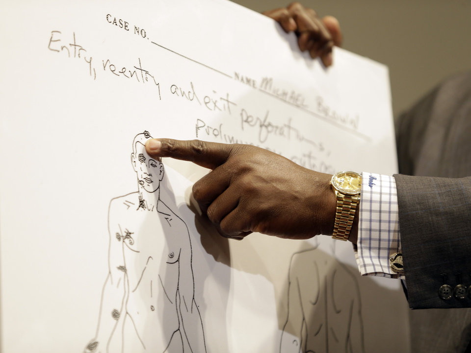 Photo - Brown family attorney Daryl Parks points to a diagram produced during a second autopsy done on Michael Brown, Monday, Aug. 18, 2014, in St. Louis County, Mo. The independent autopsy shows 18-year-old Brown was shot at least six times. (AP Photo/Jeff Roberson)