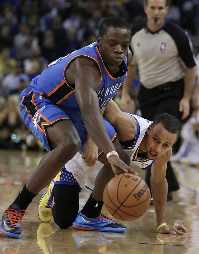Photo - Oklahoma City Thunder's Reggie Jackson, left, and Golden State Warriors' Stephen Curry chase a loose ball during the first half of an NBA basketball game Thursday, Nov. 14, 2013, in Oakland, Calif. (AP Photo/Ben Margot)