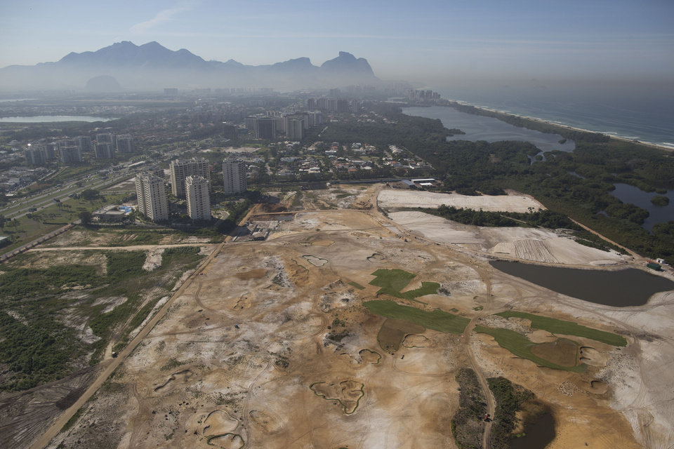 Photo - This June 27, 2014 aerial view shows, the Rio 2016 Olympic golf course under construction near the Athletes Village for the Rio 2016 Olympic and Paralympic Games in Rio de Janeiro in Rio de Janeiro, Brazil. Olympic golf course faces an uncertain future after a court proposed Wednesday, Sept. 3, 2014 that the under-construction layout should be modified to meet environmental concerns. Judge Eduardo Klausner, hearing a lawsuit brought against the city of Rio de Janeiro and the course developer, said the defendants had to return on Sept. 17 to say if they could accept the proposal. Klausner said work on the course could continue, but no new areas of vegetation could be plowed under. (AP Photo/Leo Correa)