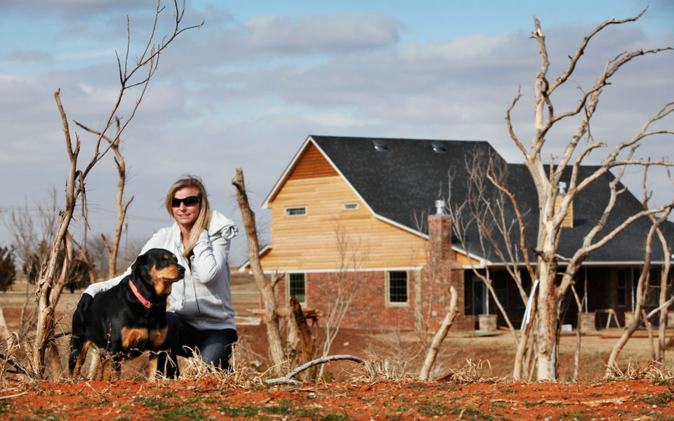 Tiffany Johnson sits with her pet rottweiler, Dutchess, on a hill across the creek and a few hundred yards south of the home she and her husband, Duane, are rebuilding near Waterloo and Sara Roads after their previous home was destroyed in a EF-5 tornado in May of 2011. The photo was taken Wednesday, Jan. 11, 2012, Photo by Jim Beckel, The Oklahoman