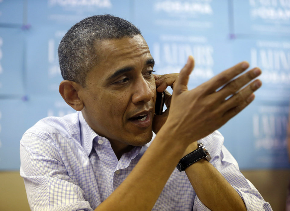 Photo -   President Barack Obama makes phone calls to supporters during a visit to a local campaign office, Monday, Oct. 1, 2012 in Henderson, Nev. (AP Photo/Pablo Martinez Monsivais)