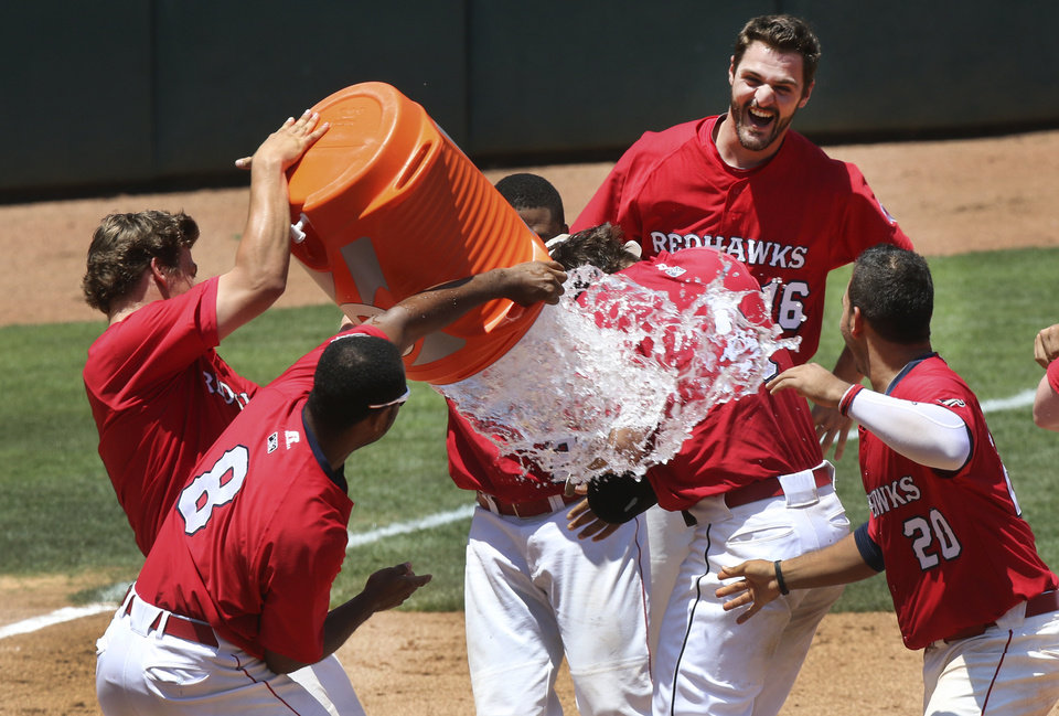 The Redhawks' pour water on Matt Duffy, center after driving in the winning run during their game against the Salt Lake Bees at the Chickasaw Bricktown Ballpark in Oklahoma City, Wednesday June 11, 2014. Photo By Steve Gooch, The Oklahoman