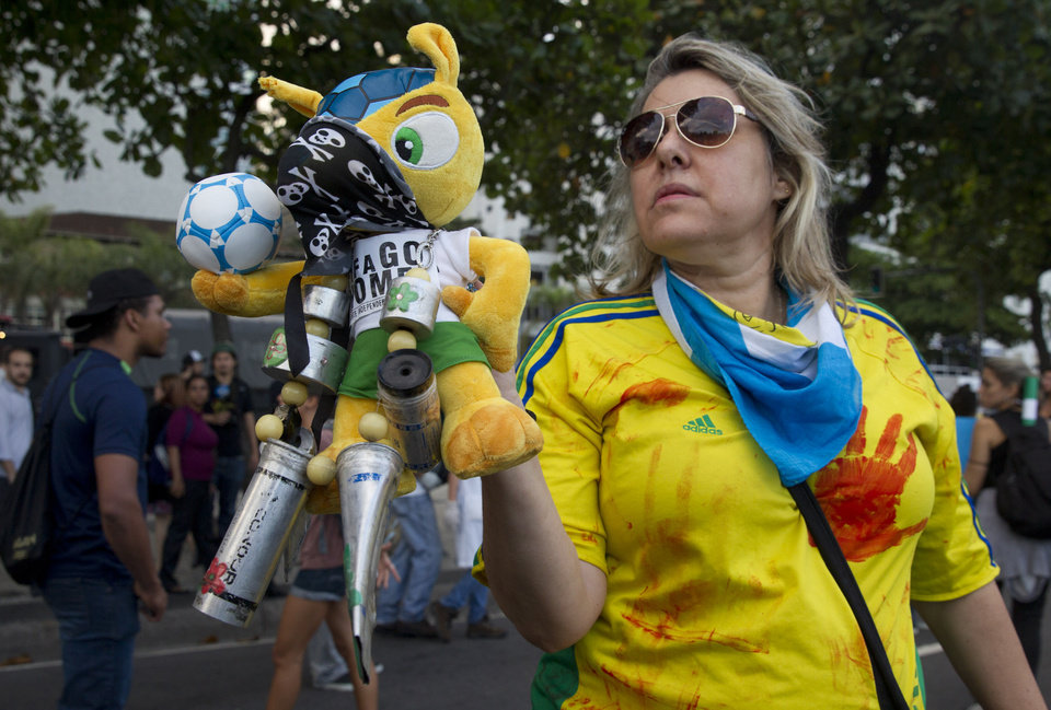 Photo - A demonstrator holds a masked doll of the mascot of the World Cup