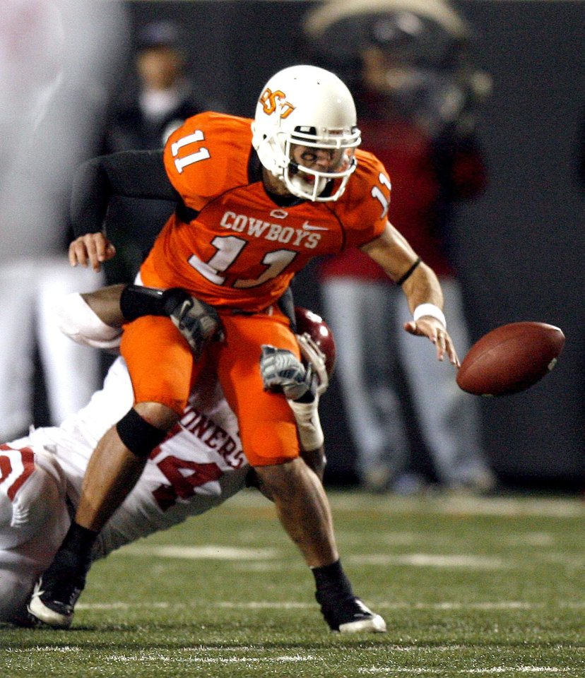Oklahoma State's Zac Robinson (11) fumbles the ball as he is tackled by Oklahoma's Jeremy Beal (44) during the second half of the college football game between the University of Oklahoma Sooners (OU) and Oklahoma State University Cowboys (OSU) at Boone Pickens Stadium on Saturday, Nov. 29, 2008, in Stillwater, Okla. STAFF PHOTO BY SARAH PHIPPS