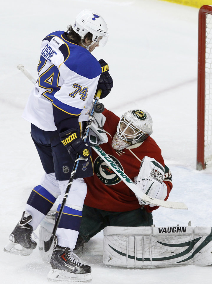 Photo - A shot goes wide past Minnesota Wild goalie John Curry, right, and St. Louis Blues right wing T.J. Oshie (74) during the first period of an NHL hockey game in St. Paul, Minn., Thursday, April 10, 2014. (AP Photo/Ann Heisenfelt)