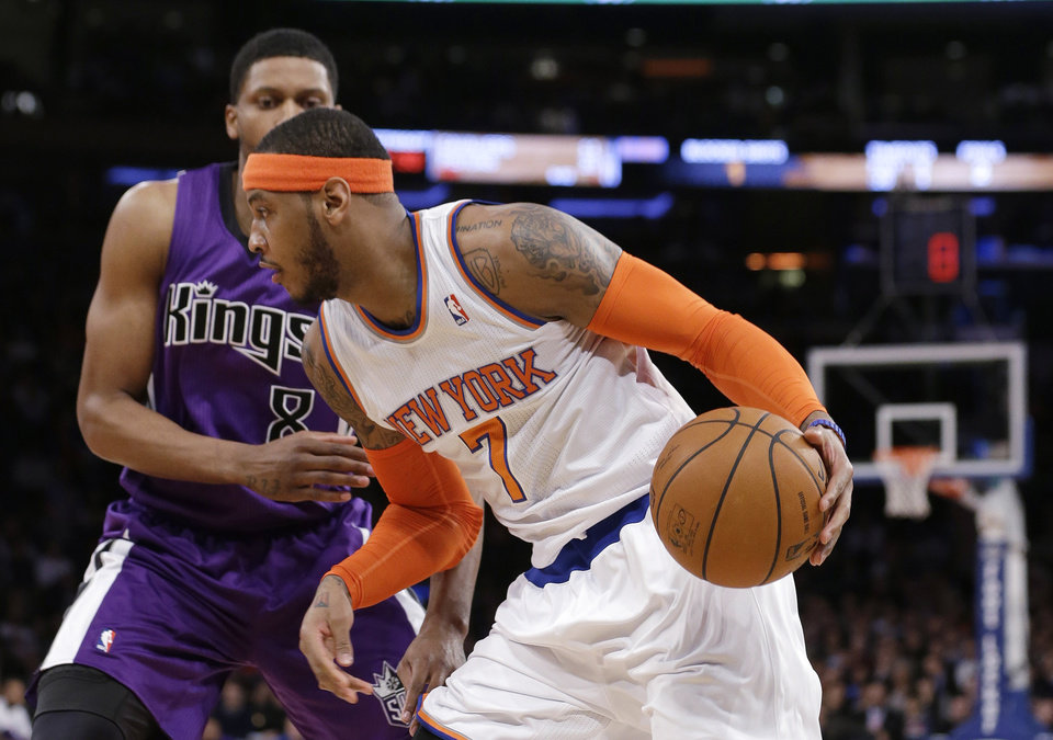 Photo - New York Knicks' Carmelo Anthony drives past Sacramento Kings' Rudy Gay during the first half of an NBA basketball game Wednesday, Feb. 12, 2014, in New York. (AP Photo/Frank Franklin II)