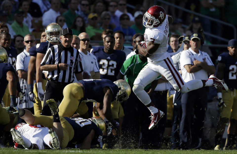 Oklahoma's Sterling Shepard (3) leaps to avoid a tackle by Notre Dame players during the first half of an NCAA college football game on Saturday, Sept. 28, 2013, in South Bend, Ind. (AP Photo/Darron Cummings) ORG XMIT: INDC111