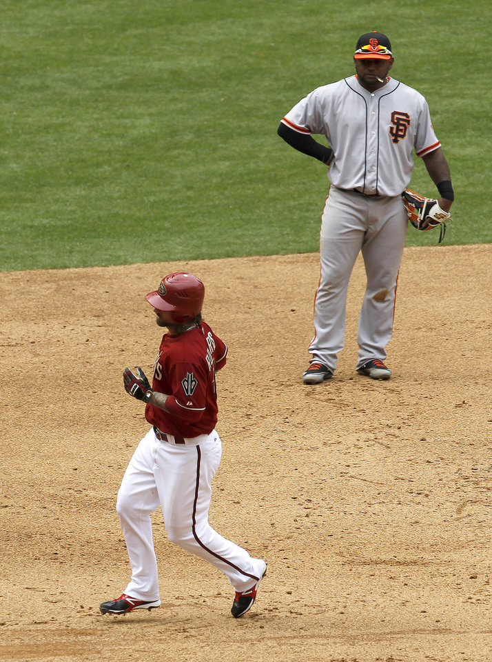Photo -   Arizona Diamondbacks' Ryan Roberts, left, rounds the bases after hitting a home run as San Francisco Giants' Pablo Sandoval looks on during the sixth inning in an MLB baseball game Sunday, April 8, 2012, in Phoenix.(AP Photo/Ross D. Franklin)