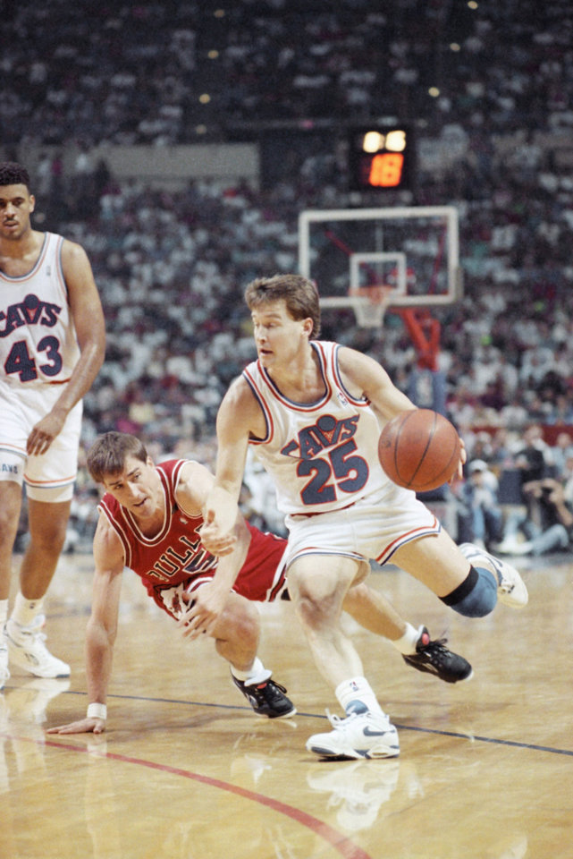 Photo - Cleveland Cavaliers guard Mark Price (25) drives around John Paxson of the Chicago Bulls in Game 4 of the NBA Eastern Conference Championships, Monday, May 26, 1992, Richfield, Ohio. Price scored 13 points in 30 minutes of action despite suffering from a stomach virus as Cleveland evened the series 2-2 with a 99-85 victory. (AP Photo/Lennox McLendon)