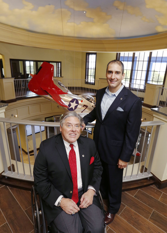 Photo -  Delaware Resource Group Chairman and CEO Phil G. Busey Sr., left, and Philip Busey Jr., senior vice president and chief communications officer, show the atrium and replica P-51 Mustang fighter plane honoring the Tuskegee Airmen, at the new DRG headquarters at 3220 Quail Springs Parkway.  [PHOTO BY PAUL HELLSTERN, THE OKLAHOMAN]