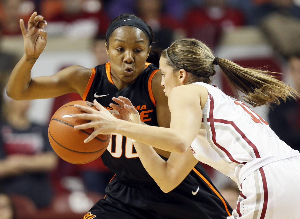 Photo - Oklahoma's Morgan Hook (10) drives against Oklahoma State's Roshunda Johnson (00) in the first half during a women's Bedlam college basketball game between the Oklahoma State University Cowgirls (OSU) and the University of Oklahoma Sooners (OU) at Lloyd Noble Center in Norman, Okla., Saturday, Feb. 1, 2014. Photo by Nate Billings, The Oklahoman