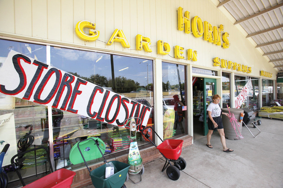 Photo - Horn Seed Co. customer Trish Collins carries a pink flamingo out the front door. The business is closing after 91 years.  Steve Gooch - The Oklahoman
