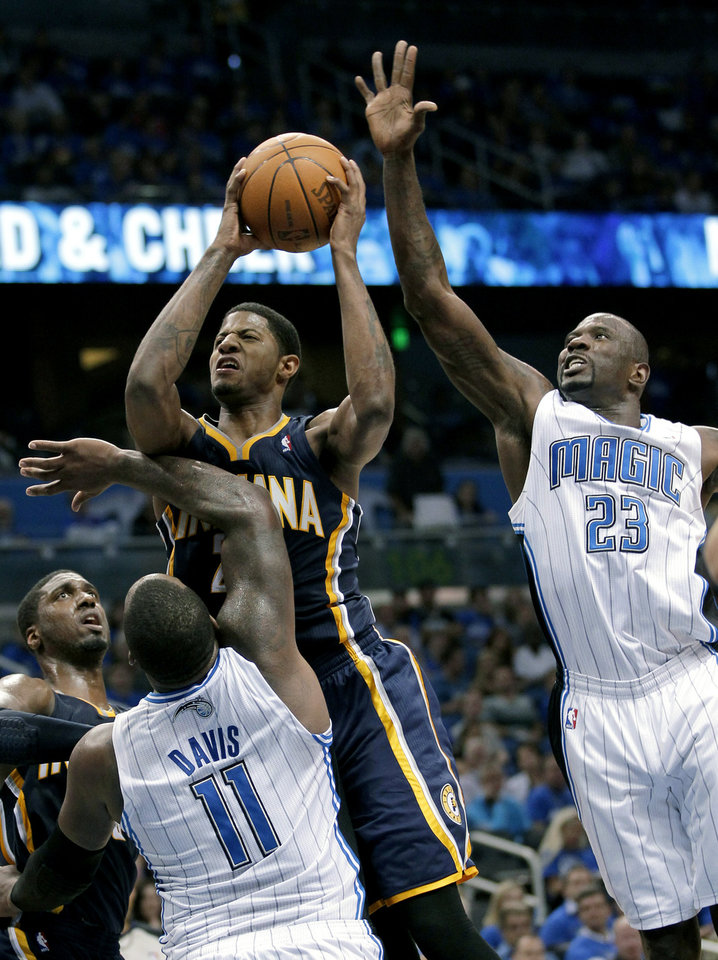 Photo -   Indiana Pacers' Paul George, center, gets off a shot between Orlando Magic's Glen Davis (11) and Jason Richardson (23) during the second half of Game 3 of an NBA first-round playoff basketball series, Wednesday, May 2, 2012, in Orlando, Fla. Indiana won 97-74. (AP Photo/John Raoux)