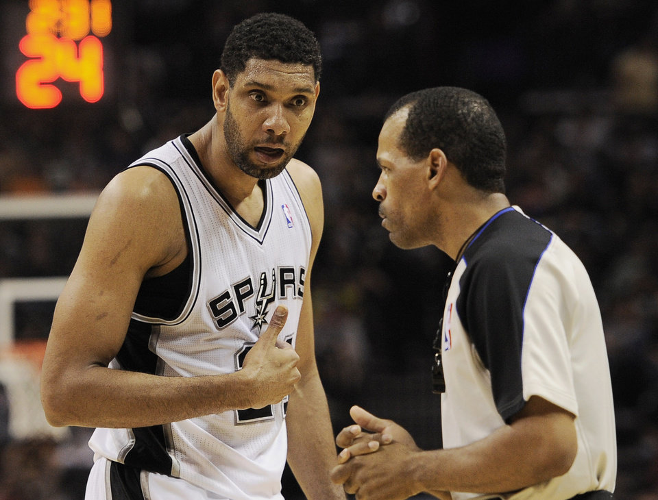 Photo - San Antonio Spurs forward Tim Duncan, left, talks to official Eric Lewis during the first half of an NBA basketball game against the Golden State Warriors, Wednesday, April 2, 2014, in San Antonio. (AP Photo/Darren Abate)