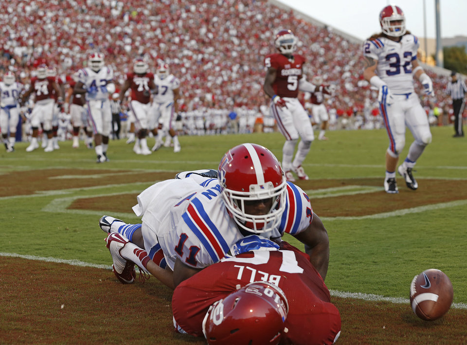 Photo - Oklahoma's Blake Bell (10) can't hold on for the completion as Louisiana Tech's Lloyd Grogan (11) is called for a penalty during a college football game between the University of Oklahoma Sooners (OU) and the Louisiana Tech Bulldogs at Gaylord Family-Oklahoma Memorial Stadium in Norman, Okla., on Saturday, Aug. 30, 2014. Photo by Bryan Terry, The Oklahoman