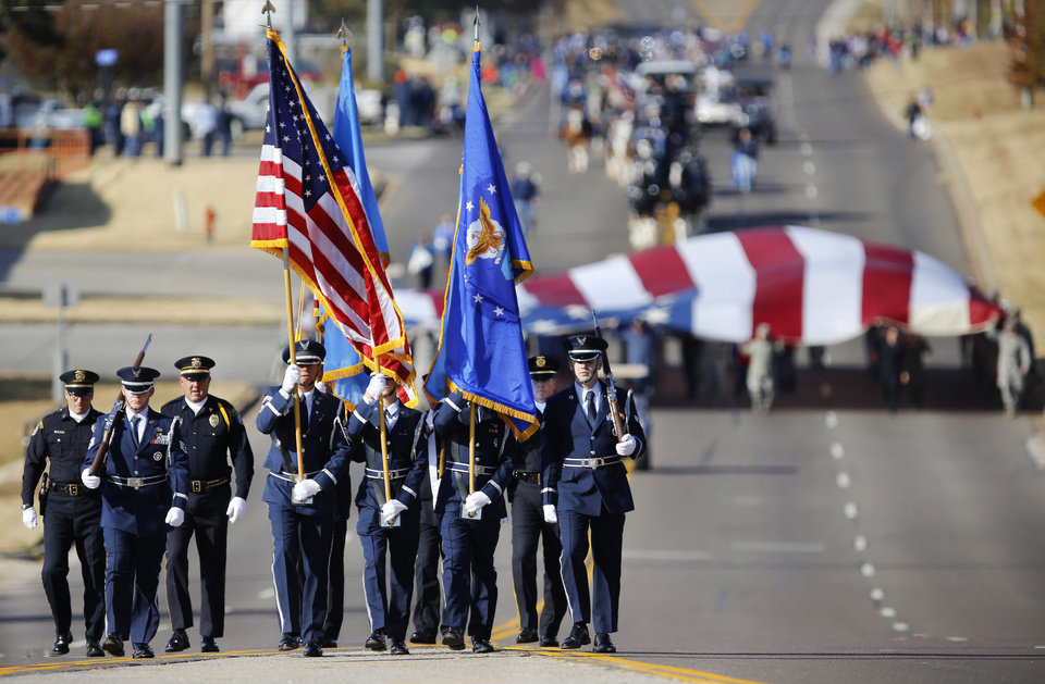 Photo - Air Force and Midwest City Police honor guards lead the Midwest City Veteran's Day Parade as it moves east on SE 15 Street near Douglas Blvd. on Friday, Nov. 10, 2017. Photo by Jim Beckel, The Oklahoman