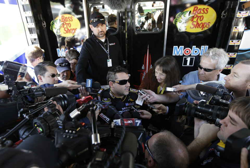 Driver Tony Stewart is swarmed by the media as he answers questions for after practice Sunday's NASCAR Sprint Cup auto race at Martinsville Speedway in Martinsville, Va., Friday, April 5, 2013.  (AP Photo/Steve Helber)