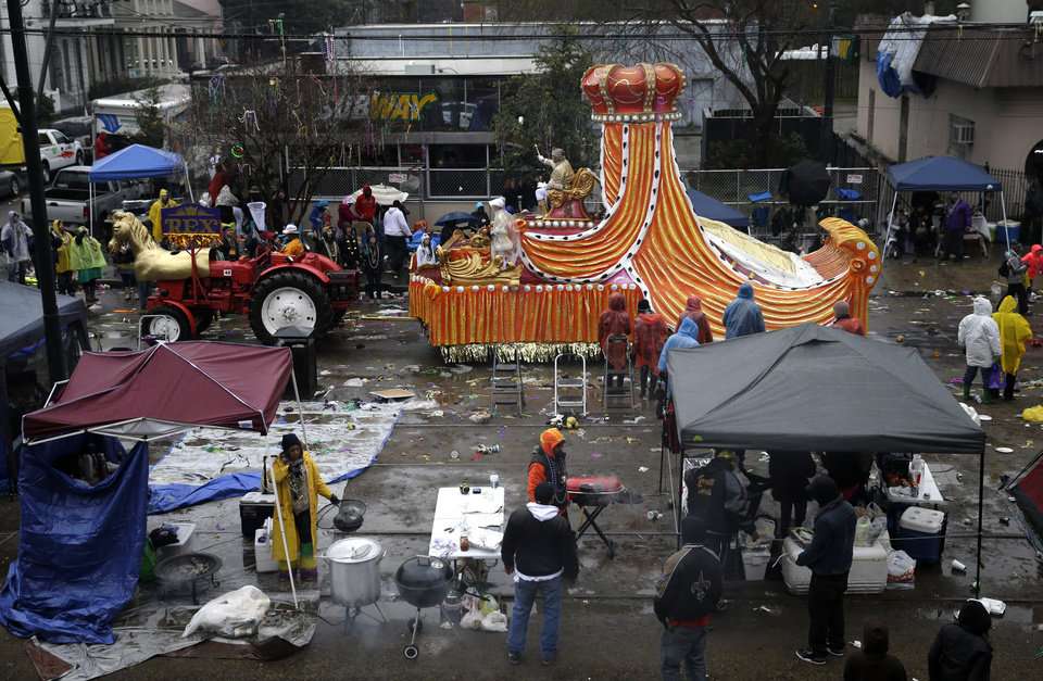 Photo - King of the Krewe of Rex, Jack Laborde, rides on his float down a largely empty St. Charles Ave., during Mardi Gras day in New Orleans, Tuesday, March 4, 2014. Rain and unusually cold temperatures kept the normally massive and festive crowds away. (AP Photo/Gerald Herbert)