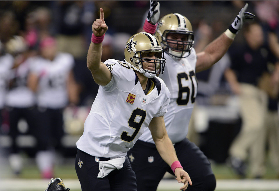 New Orleans Saints quarterback Drew Brees (9) reacts after completing a touchdown pass for his 48th consecutive game, breaking Johnny Unitas' NFL record which stood for over 50 years, during an NFL football game against the San Diego Chargers at the Mercedes-Benz Superdome in New Orleans, Sunday, Oct. 7, 2012. (AP Photo/Bill Feig)