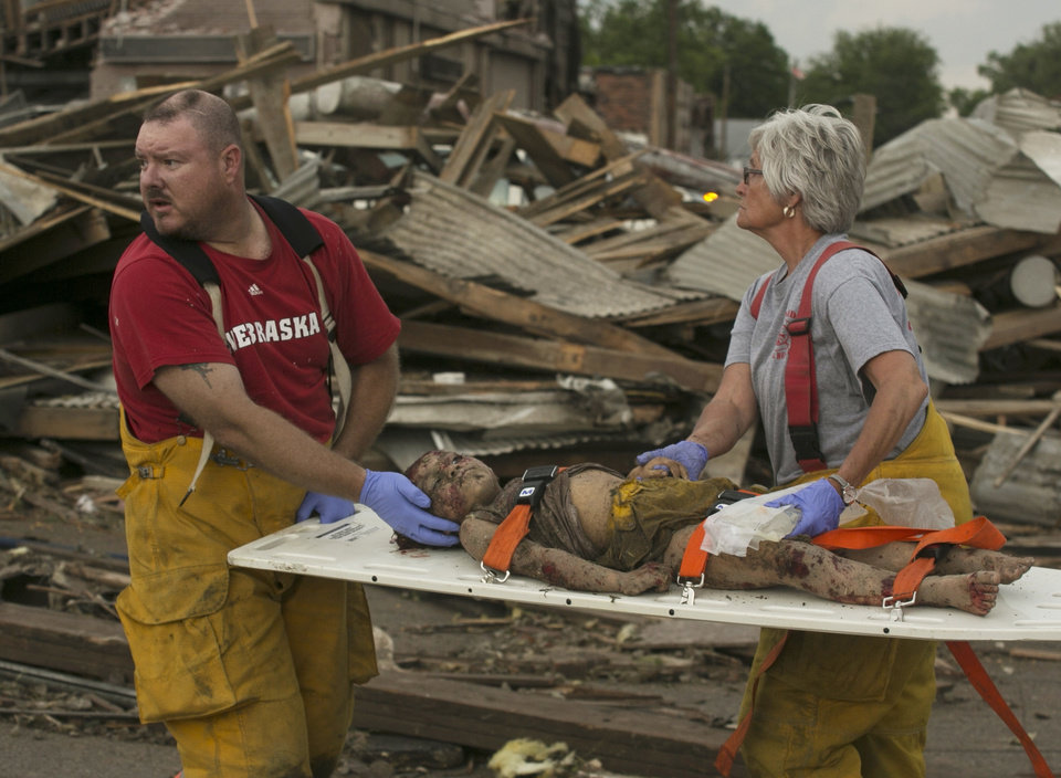 Photo - Rescue personnel tend to a young tornado victim in  Pilger, Neb., Monday, June 16, 2014. A hospital spokeswoman says at least one person is dead and at least 16 more are in critical condition after two massive tornadoes swept through northeast Nebraska. (AP Photo/Mark 'Storm' Farnik)