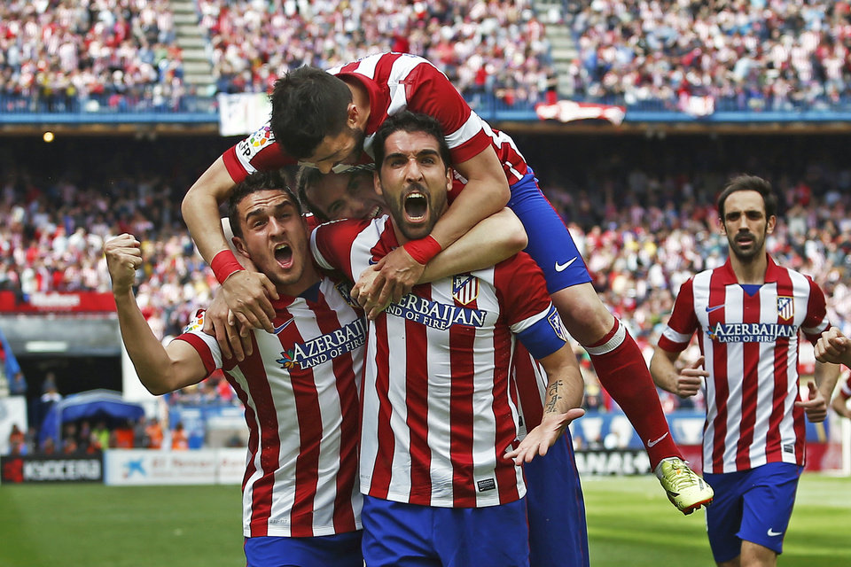 Photo - Atletico's Raul Garcia, center right, celebrates his goal with teammates during a Spanish La Liga soccer match between Atletico Madrid and  Villarreal at the Vicente Calderon stadium in Madrid, Spain, Saturday, April 5, 2014. (AP Photo/Andres Kudacki)