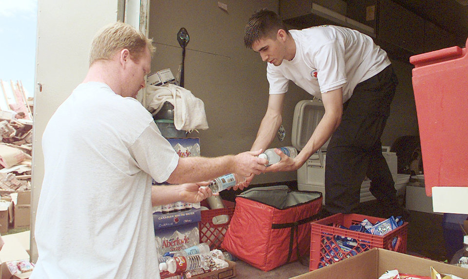 MAY 3, 1999 TORNADO: NORMAN RED CROSS VOLUNTEER JASON HOLASEK HANDS OUT FOOD AND WATER TO BRANDON HALL, A TORNADO VICTIM.