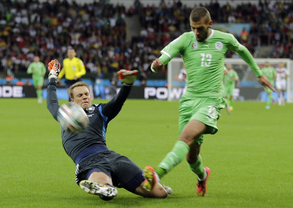 Photo - Germany's goalkeeper Manuel Neuer, left, slides in to make a save against Algeria's Islam Slimani during the World Cup round of 16 soccer match between Germany and Algeria at the Estadio Beira-Rio in Porto Alegre, Brazil, Monday, June 30, 2014. (AP Photo/Matthias Schrader)