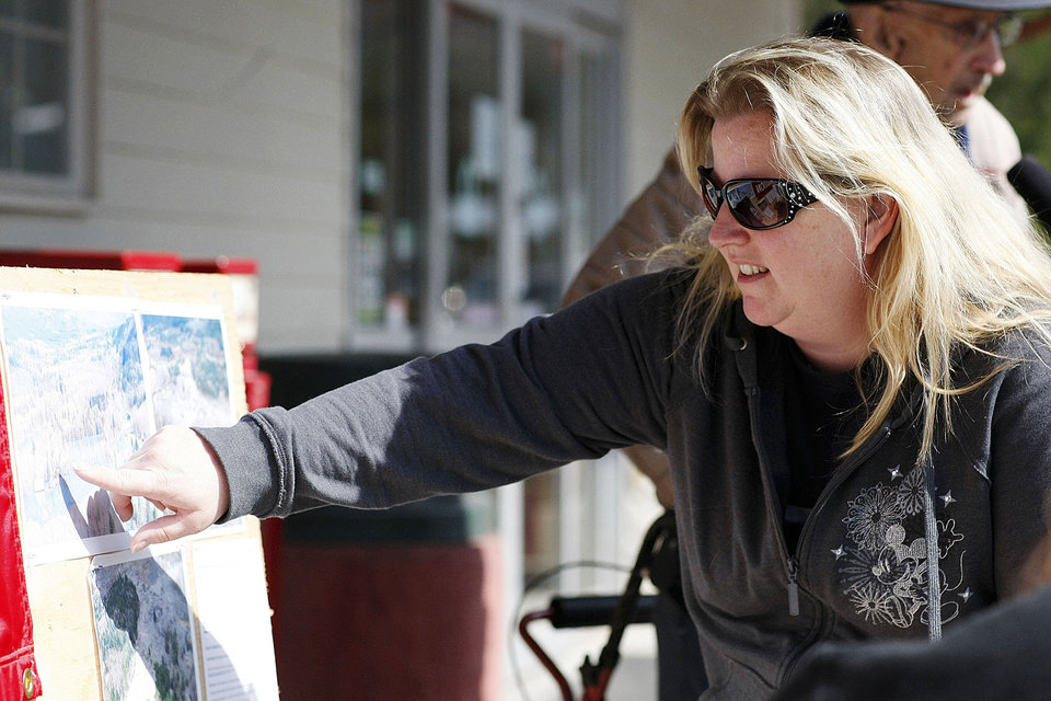 Photo - Rachel Bailey checks a map of the Oso mudslide area at the Darrington IGA market Monday, March 24, 2014, in Darrington, Wash. Friends of Bailey are still missing from the mudslide.   (AP Photo /The Herald, Sofia Jaramillo)