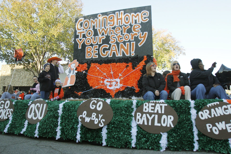 Photo - OSU fans ride a float in the Oklahoma State Cowboy's homecoming parade in downtown Stillwater, OK, Saturday, Oct. 29, 2011. By Paul Hellstern, The Oklahoman