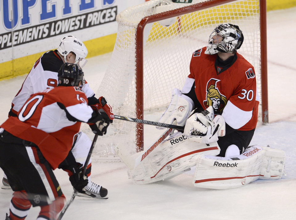 Photo - Ottawa Senators goalie Robin Lehner reacts as he is hit with the stick of New Jersey Devils center Harri Pesonen under pressure from Ottawa Senators' Mike Lundin during second period NHL action in Ottawa, on Monday March 25, 2013.  (AP Photo/The Canadian Press, Adrian Wyld)