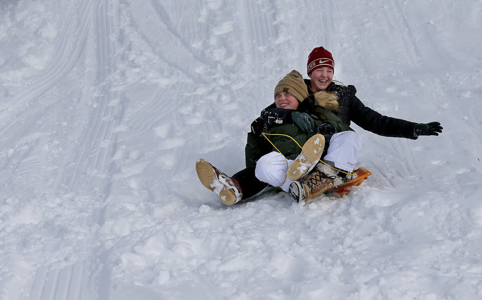 Photo - Layne Patterson and Farrah Enright sled on a hill along Hefner Road in Oklahoma City, Wednesday, Feb. 17, 2021. [Sarah Phipps/The Oklahoman]