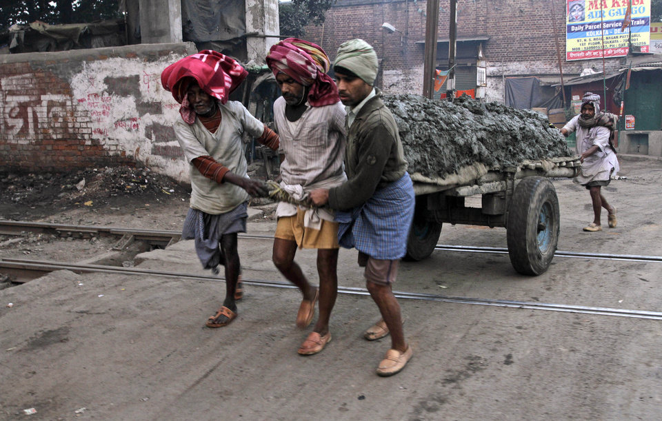 Indian laborers pull a mud-filled handcart over a railway track on a cold winter morning in Kolkata, India, Friday, Jan. 11, 2013. More than 100 people have died of exposure as several parts of India deal with historically cold temperatures. (AP Photo/Bikas Das)