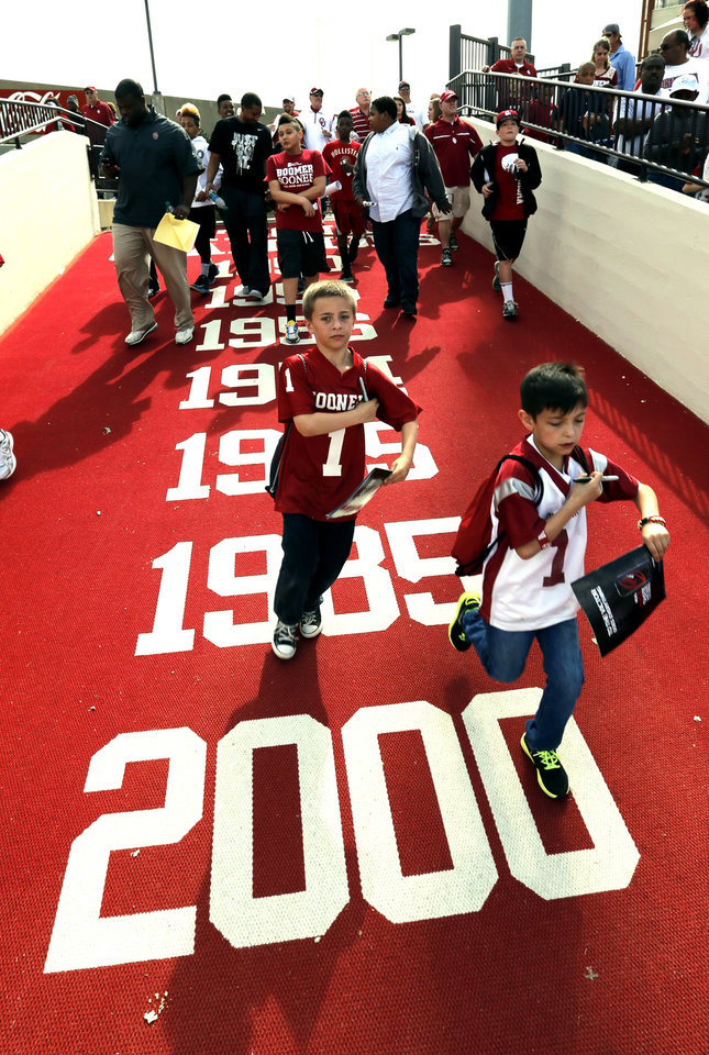 Photo - Fans run onto the field for autographs after the annual Spring Football Game at Gaylord Family-Oklahoma Memorial Stadium in Norman, Okla., on Saturday, April 13, 2013. Photo by Steve Sisney, The Oklahoman