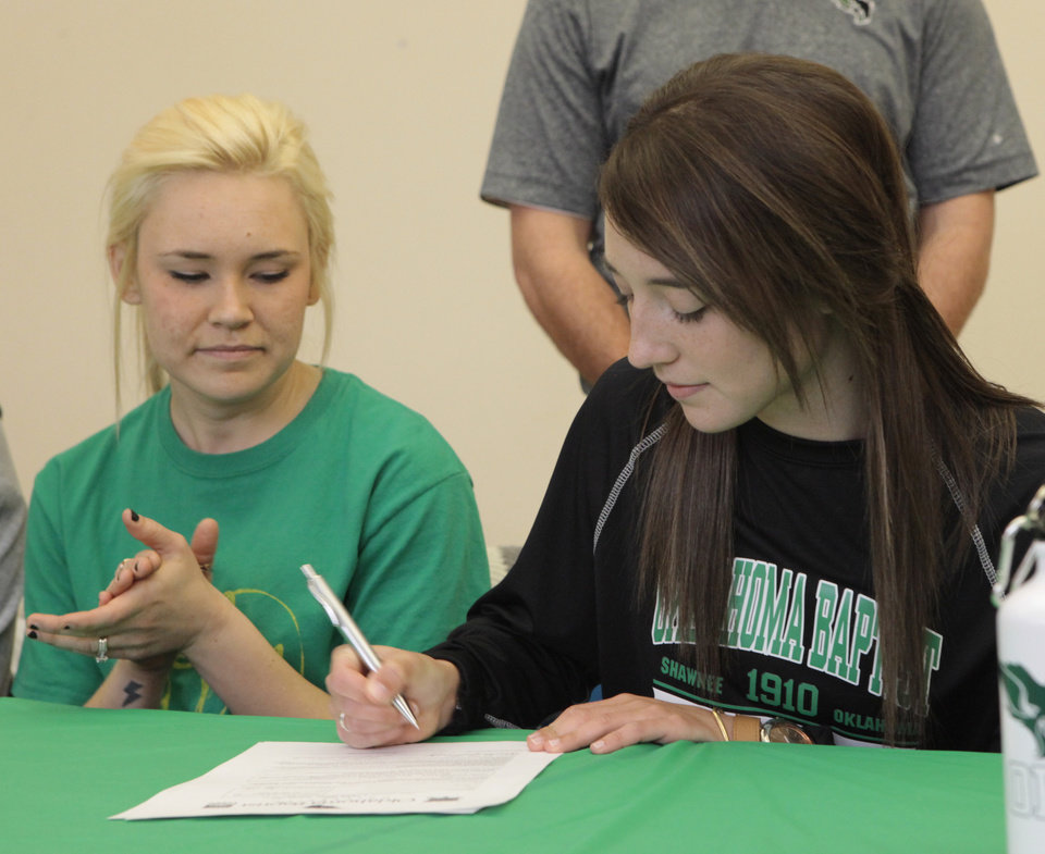 Mikayla Lowery, right, signs a letter of intent wit OBU, while her sister Katie Puckett claps, at day at Deer Creek High School, Wednesday, February 4, 2014.  Photo by David McDaniel, The Oklahoman