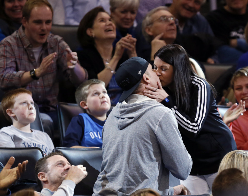 Photo - A couple get engaged during a break in the action at an NBA basketball game between the Memphis Grizzlies and the Oklahoma City Thunder at Chesapeake Energy Arena in Oklahoma City, Friday, Feb. 28, 2014. Photo by Nate Billings, The Oklahoman